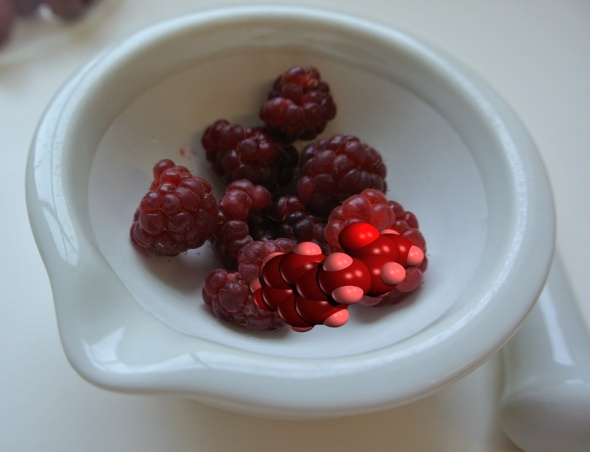 Raspberries and a molecule of raspberry ketone (4-(4-Hydroxyphenyl)butan-2-one) in a mortar, with the pestle lying next to it.